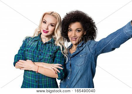 Two beautiful girls making selfie. Isolated on white background. young woman looking into the camera