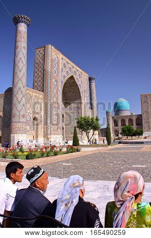 SAMARKAND, UZBEKISTAN - MAY 21, 2011: The Registan with Uzbek men and women traditionally dressed in the foreground