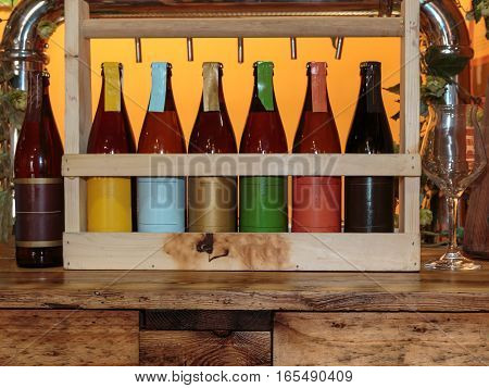 Colorful Beer Bottles On Wooden Table And Orange Background