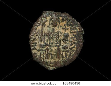 Ancient Copper Byzantine Copper Coin With Figure On It Isolated On Black
