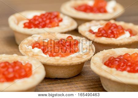 Several tartlets with red caviar and butter on wooden brown table macro
