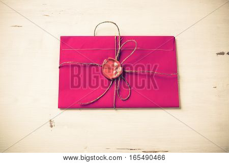Pink letter envelope with wax seal on wooden surface