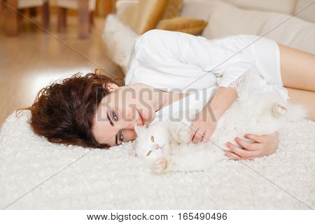 Cute curly girl in a white silk dressing gown in the early morning playing with white fluffy cat sitting on sofa