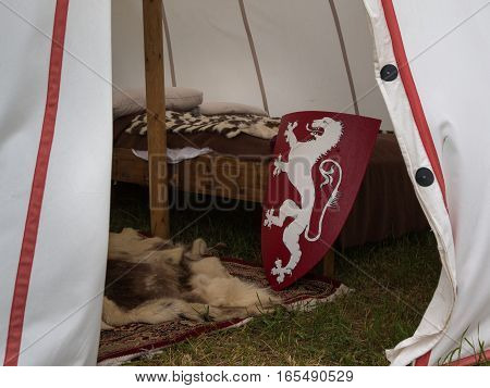 Inside Medieval Tent: Wodden Bed Carpet and Red Shield with Dragon - Medieval Event Reconstruction