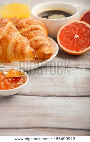 Fresh Croissants with coffee, jam and orange juice for breakfast on rustic wooden background, selective focus, copy space