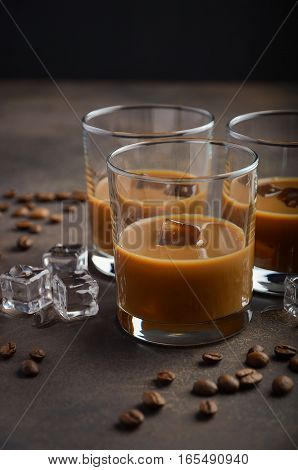 Glass of Coffee Liqueur with ice on the old rusty background, selective focus, copy space