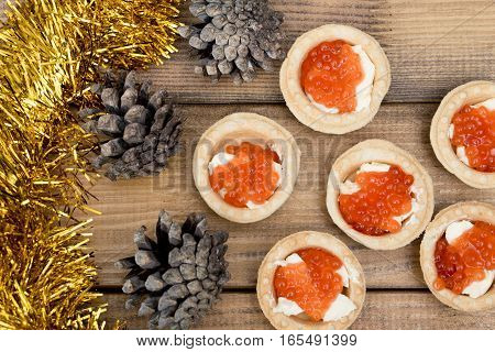 Several tartlets with red caviar and butter tinsel fir coneson wooden brown table top view