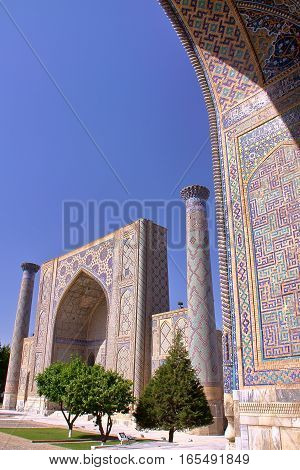 SAMARKAND, UZBEKISTAN: The Registan with architectural detail of a madrasa in the foreground