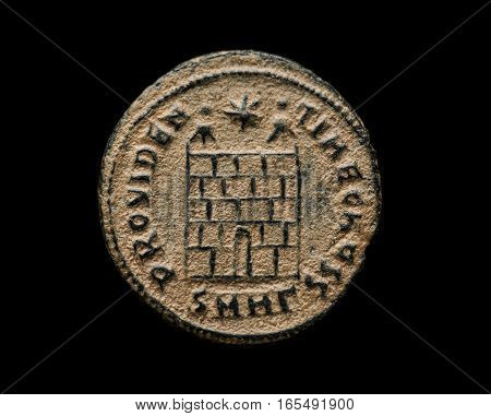 Ancient Roman Copper Coin With Fortress Image On It Isolated Om Black