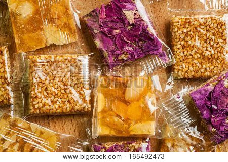 Close-up Shot Of Oriental Sweets In Plastic Package On Wooden Table