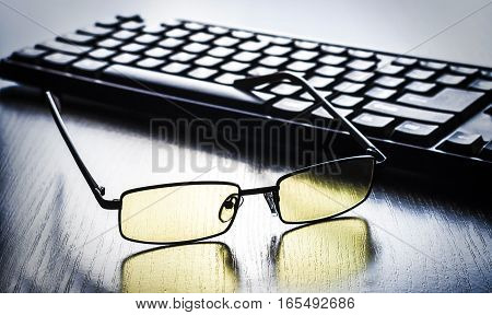 yellow glasses to eye protection near the keyboard