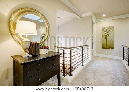 Second Floor Landing With Black Console Table And Round Gold Mirror.