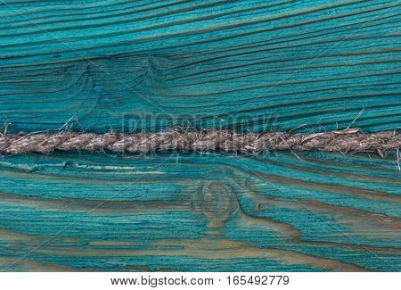 blue wooden texture background with old rope, close up