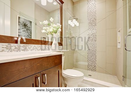 White and clean bathroom design in brand-new home. Glass walk-in shower with white subway tiled surround accented with vertical mosaic tile strip. Northwest USA