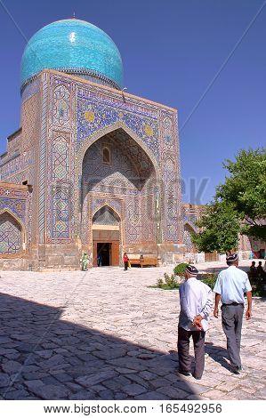 SAMARKAND, UZBEKISTAN - MAY 21, 2011: Two Uzbek men with an Uzbek hat walking in the courtyard of a madrasa at the Registan