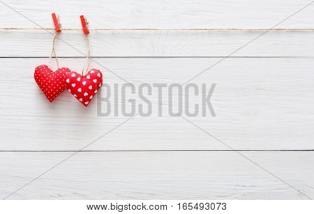 Valentine background with sewed pillow hearts couple on red clothespins at rustic white wood planks. Happy lovers day card mockup, copy space on wooden surface, shabby chic style