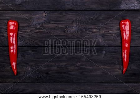Red chili pepper on the dark wood background