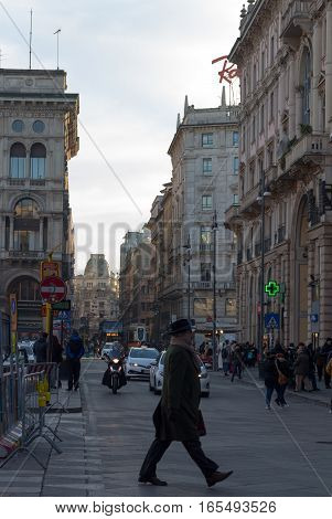 MILAN, ITALY - January 13, 2016: An older man crossing the street in center of Milan, Italy. A lot of traffic passing in the background