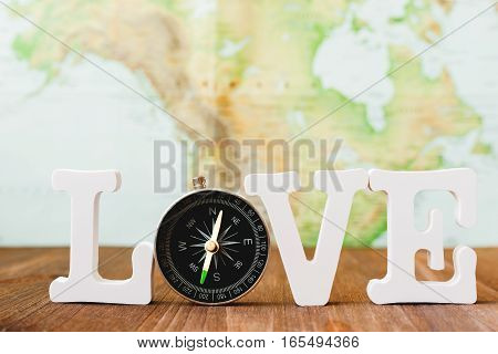 Love to travel. Word with magnetic compass. Blurred world map as background. Place for text.