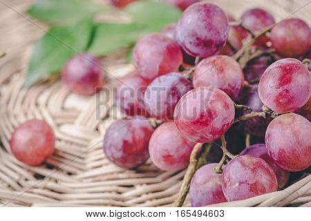 purple round grapes on wicker baskets vintage. Bunches of fresh ripe red grapes on a wooden textural surface. Ancient style, a beautiful background with a branch of blue grapes. Red wine grapes. dark grapes, blue grapes, wine grapes
