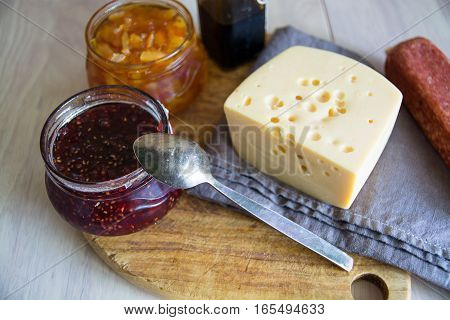 Big piece of cheese salami and jars with jam. Wooden cutting board.