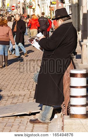 MOSCOW RUSSIA - March 25 2007. Man reading paper people walking on Arbat street. Warm and sunny spring day.