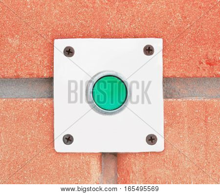 Close-up of pressing the button of a doorbell on a wall background