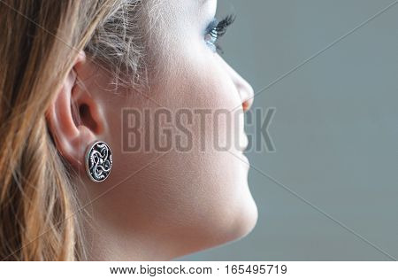 Earring on model's ear. Beautiful model brunette with long hair and jewelry wearing earring