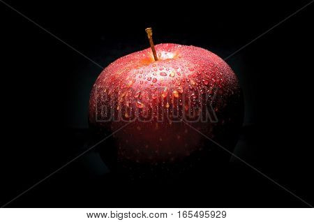 red apple with drops on black background