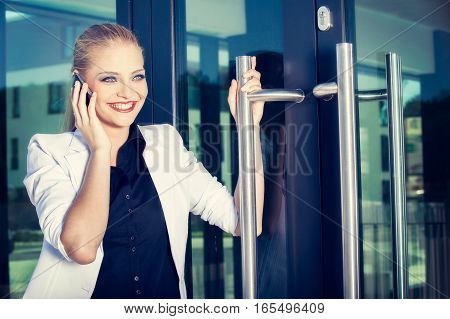 Young Business Woman Talking A Mobile Phone On Street Against Building