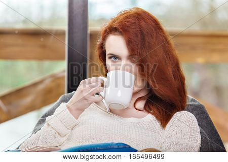 Atractive Red-haired Woman Drinking Cup Of Coffee Sitting On Rocking Chair. Young Girl With Hot Ener