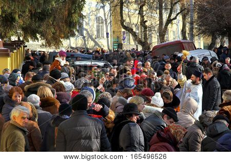 Uzhgorod Ukraine - January 19 2016: A priest (R) blesses Greek Catholic parishioners during the celebration of Holy Epiphany Day. After a festive divine service thousands of Orthodox parishioners traditionally bathed in ice-hole in water reservoirs.