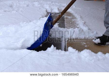 Manual clearing snow rake sidewalk. Winter time.