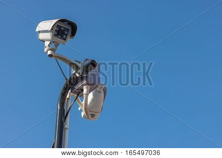 Close circuit camera. The close circuit camera on the pole with the blue sky background. The security system from the close-circuit camera with the sky.