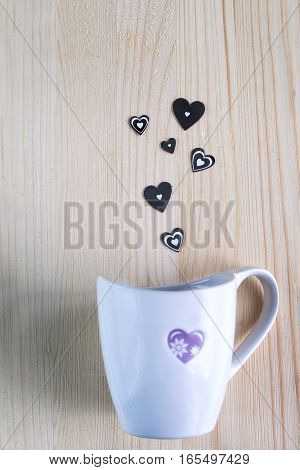 Departing silver heart from a Cup on the background of wooden boards, Valentine's day