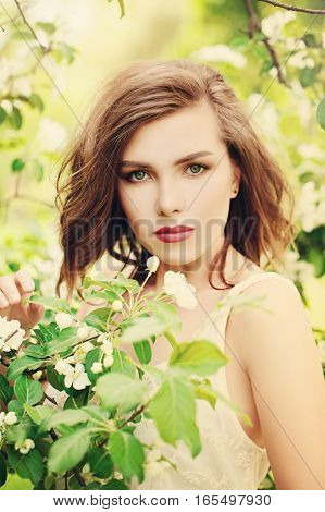 Cute Girl in Spring Park. Fashion Model Woman on Flowers and Green Leaves Background