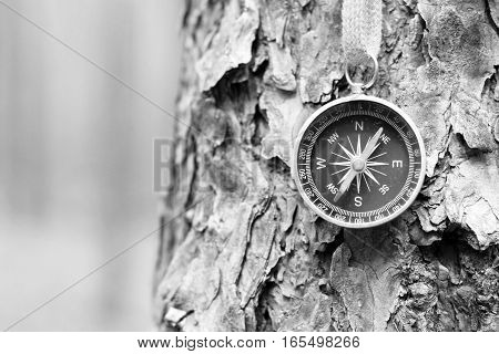 Black and white photo of an old compass in retro style / tourist compass closeup