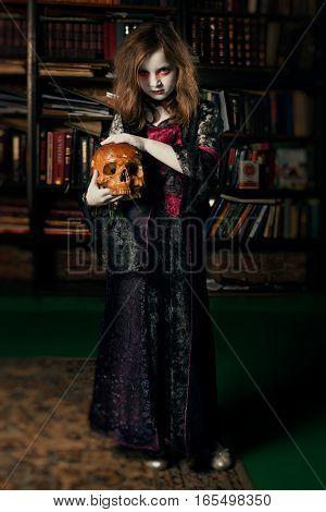 Little girl vampire in library holding in hand the human skull