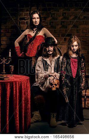 Vampire family indoors on small brick background