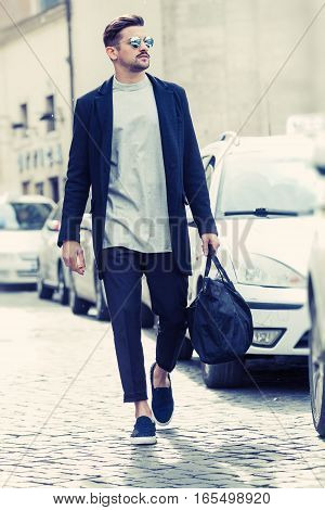 Cool man beautiful model outdoors, city style fashion. A handsome man model walking in the city center next to some cars. urban setting. The young boy as trendy, modern clothing with bag. Cobblestones to the ground.