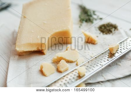 Parmesan piece closeup with small grater. Classic italian cuisine cooking ingredient, grated hard cheese. Shallow depth of field, selective focus
