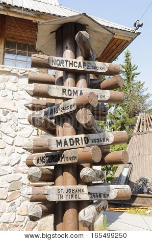 A wooden signpost in Santa Claus Village Rovaniemi Lapland Finland showing distances of some of the most important European cities from the Arctic Circle