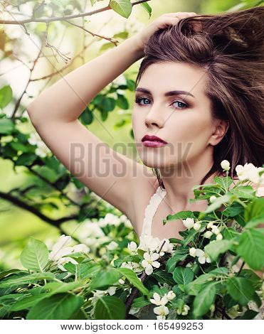Spring Model Young Woman with Blowing Hairstyle on Blossoms Background. Young Beauty Outdoors