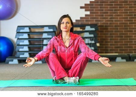 Young Beautiful White Girl In A Pink Sports Suit Meditates On The Yoga Class At The Fitness Center.