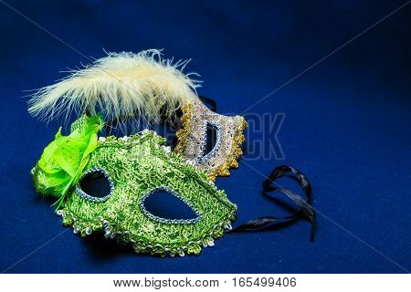 Theatrical masks with ornaments a feather against a dark background
