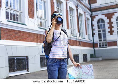 Cheerful woman making photo traveling abroad in summer happy female siteseeing in a foreign city during vacation