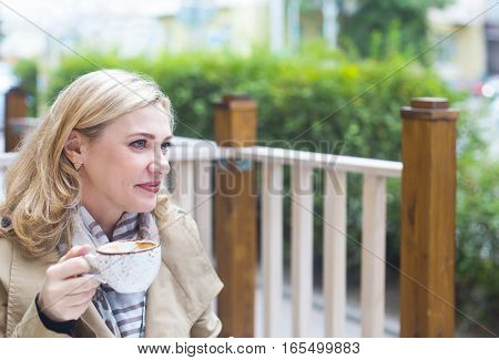 Close up happy middle age blond woman with cup of coffee looking into distance.