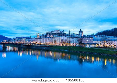 Evening twilight view of historic city of Salzburg with illuminated Cathedral and Hohensalzburg Fortress Festung across Salzach river in Austria