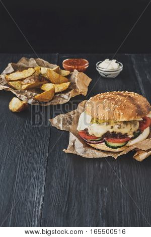 Fast food restaurant dish top view. Meat cheese burger in craft paper, potato chips and wedges. Meals on dark black wood background. Hamburger and spicy tomato sauce. Vertical, filtered