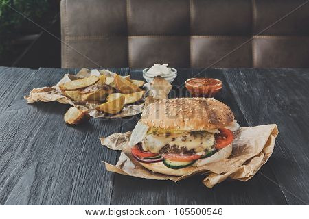 Fast food restaurant dish top view. Meat cheese burger in craft paper, potato chips and wedges. Take away set on dark black wood background. Hamburger and spicy tomato sauce. Filtered